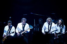 A color photograph of four members of the Eagles on stage with guitars