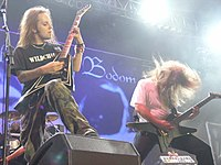 "A color photograph of two members of the group Children of Bodom standing on a stage with guitars, drums are visible in the background. Both electric guitarists have ""flying V"" style guitars and they have long hair."