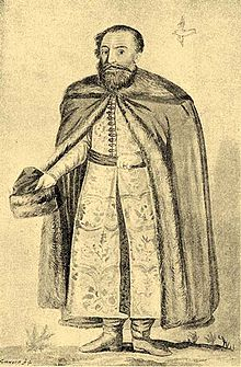 An elderly bearded man with a hat in his hand wearing a coat decorated with furs