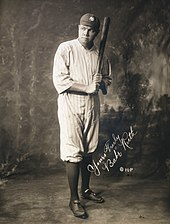 "A man in full baseball attire wears a pinstriped jersey and a hat with overlapping white ""N"" and ""Y"". Looking to the left of the camera, he is holding a baseball bat upward."