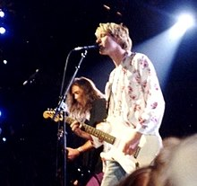 A color photograph of two members of the band Nirvana on stage with guitars