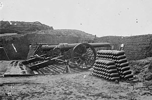 two cannon on a ground level platform with two stacks of percussion shells
