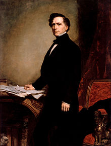 Franklin Pierce, a man with brown hair and a blacks suit, stands with his right hand resting upon papers on a table.