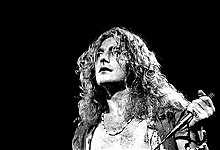 A black and white photograph showing a headshot of Robert Plant with a microphone in hand