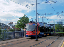 A Sheffield Supertram in current blue, orange and red Stagecoach livery. The Tram shown is cross the Park Square junction. Behind it is the bridge connecting the junction and tracks to Sheffield city centre. The whole square (now 20 years since redevelopment) is covered in trees and plants and new buildings can be seen beyond them.