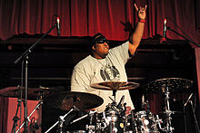 The drummer from the band Suicidal Tendencies, Eric Moore, is shown behind his drumkit. One hand is raised with the index finger and pinky extended.