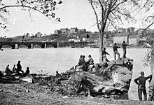 Black-and-white photo of several military men idling on a riverbank. Across the river are several large buildings.