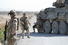 Canadian Grenadier Guards in Kandahar Province standing by a road with armoured car