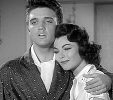 Black-and-white screenshot of a man and woman standing next to each other. The man has his arm around the woman's shoulders as she smiles.