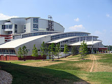 A large, white, multi-story building constructed from concrete, metal and glass with several tiered, curved roof segments framing long panels of windows. The building is set back on a large green lawn with several small pine trees
