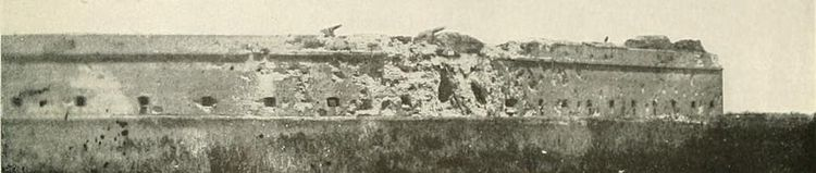 panoramic photo across swamp showing pot-marked fort (a) south wall (left) and (b) east wall (right), (c) two large holes in southeast corner