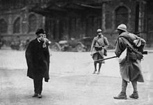 A soldier, on the right, faces a civilian, on the left. A second soldier, far center, walks towards the two.