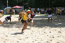 On a sunlit beach two teams of players, one in yellow the other in blue, play a form of rugby; the central yellow player runs forward clutching the ball with one hand, close to his chest.