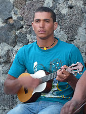 A young man holds a small four-stringed instrument and strums.