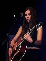 Marion Raven, a young brunette woman, playing a guitar on stage
