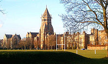 A wide shot of an old English school with a central tower, a sports pitch is seen in the foreground.