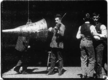 Black-and-white film screenshot of a man (at center) playing a violin while facing a large cone. An obscured man is seen behind the cone. Two men at the right are dancing with each other.