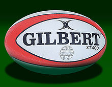 An oval shaped synthetic ball, white in colour with red trim, adorned with the manufacturers name