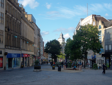 Fargate shopping precinct, Sheffield. Once a busy road, it has been pedestrianised for several decades and is Sheffield's main City Centre shopping area, home to many well-known companies. The image shows classical architecture on both sides with one plan spaces in the centre, dotted with trees and the buildings on the High Street are visible beyond the trees.
