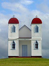Simple white building with two red domed towers