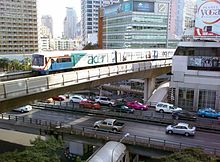 "An elevated train, painted in blue, white and a red stripe and with advertisements with the name ""acer"", running above a road lined with many tall buildings and crossing an intersection with a flyover bridge with many cars"