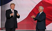 "Donald Trump and his running mate for vice president, Mike Pence. They appear to be standing in front of a huge screen with the colors of the American flag displayed on it. Trump is at left, facing toward the viewer and making ""thumbs-up"" gestures with both hands. Pence is at right, facing toward Trump and clapping."