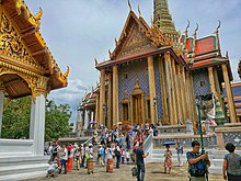 A Thai temple complex with several ornate buildings, and a lot of visitors
