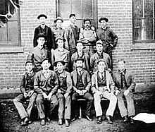 Group photo of fifteen men; five in the top row, four in the middle, and six in the front, posing in front of a brick building