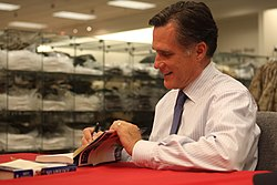 Casual photograph of Mitt Romney indoors seated and signing books