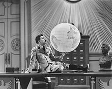A black-and-white screenshot of a man sitting upon a table, holding a globe.