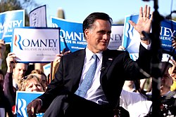 "Mitt Romney sitting outdoors during daytime, with crowd behind him holding up blue and white ""Romney"" signs"
