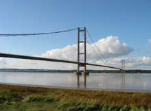 The near pier of a suspension bridge spanning calm blue waters of a wide river estuary.