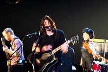 A color photograph of members of the Foo Fighters on stage with instruments