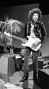 A black and white photograph of Jimi Hendrix playing a guitar