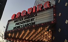 "A film marquee reading ""MISTER AMERICA / PRESENTED BY / MONEYZAP.COM"