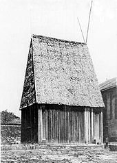 Large wooden rectangular house with steeply peaked roof in thatch