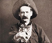 A black-and-white screenshot of a man facing the camera, while also pointing a revolver forward. He has a large mustache and is wearing a cowboy hat, a bandana around his neck, and a heavy jacket.