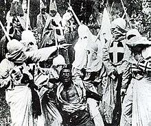 "A black-and-white screenshot of several men in white robes and hoods surrounding an African-American man (a white actor using ""blackface""). The men's robe have crosses on them and in the background other men are on top of horses."