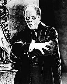 A man wearing extensive makeup is looking to his left. The makeup gives a skull-like appearance and he is wearing a robe with his arms crossed in front of him.