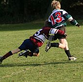 A child running away from camera in green and black hooped rugby jersey is being tackled around the hips and legs by another child in opposition kit.