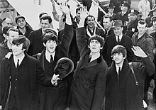 Black and white picture of the Beatles waving in front of a crowd with an set of aeroplane steps in the background