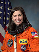An astronaut wearing her orange mission suit with the American flag embroidered on her shoulder and name tag and mission patches embroidered on her chest.