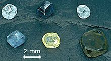 Six crystals of cubo-octahedral shapes, each about 2 millimeters in diameter. Two are pale blue, one is pale yellow, one is green-blue, one is dark blue and one green-yellow.