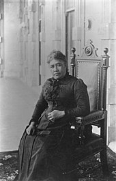 Queen Liliʻuokalani, seated inside ʻIolani Palace.