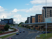 The start of the Sheffield Parkway, as viewed from Park Square, where it meets the City Centre. The road, in the centre, is six lanes wide and leads towards the Parkway Edge development (left-centre) where the road meets the Inner Ring Road. To the right is the Sheffield Supertram viaduct and beyond that a new apartment complex.
