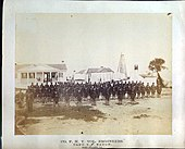 Union engineers lined up in sandy foreground of white houses, white lighthouse in the far background