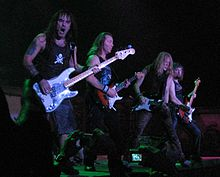 Four members of Iron Maiden are shown in concert. From left to right are a bass guitarist and then three electric guitarists. All members shown have long hair.