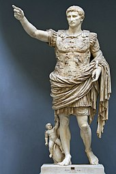 A marble statue of the Emperor Augustus. He stands with one arm raised as if in command. Augustus is depicted as a man of about thirty five, with short hair and clean shaven. He wears Roman military uniform of a breast plate, leather accoutrements and a cloak over a short tunic. The breastplate is decorated with symbolic figures. As a work of art, the statue displays high technical mastery.